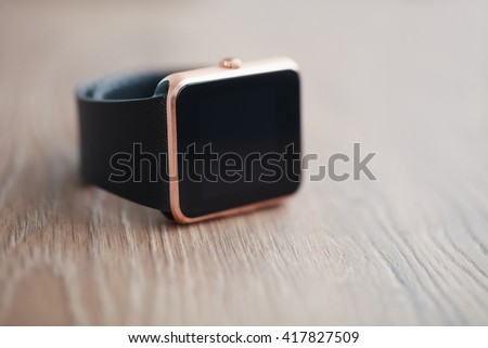 Modern unknown smart watches on wooden background. Trendy new technology that let you always stay connected to internet and social media. Place text or app icon on blank black screen. Macro close up - stock photo