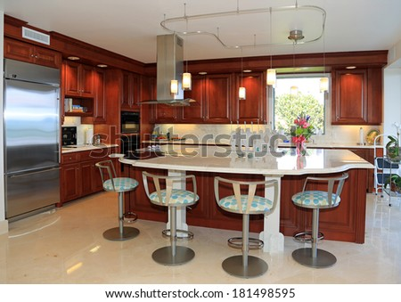 Modern, upscale kitchen with marble counter top and swivel bar stools, - stock photo
