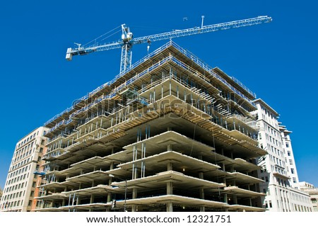 modern urban building under construction with a crane and blue sky - stock photo