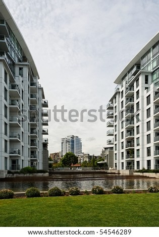 Modern urban city skyline composed of apartments and condominiums, a water filled plaza and vista to the city's skyline beyond.  Portland Oregon's Pearl District in the Pacific Northwest. - stock photo