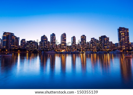 Modern Urban City Skyline Reflecting in Water at Sunset, Vancouver - stock photo
