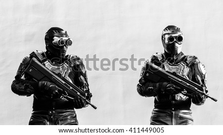 Modern urban soldiers of special elite commando units posing in special black tactical uniform with machine guns with gray concrete background - stock photo