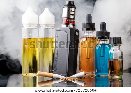 Modern vaporiser versus old tobacco cigarette in smoke cloud