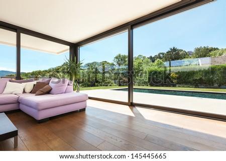 Modern villa, interior, wide living room with pink divan - stock photo