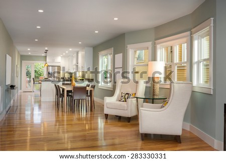 Modern villa, interior with designer chairs, table, beautiful wooden floor and open kitchen next to dining room - stock photo