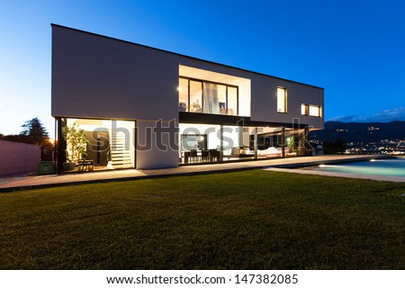 Modern villa with pool, view from garden, night scene