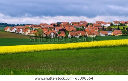 Modern village in Bavaria, Germany in spring time with yellow canola field in front - stock photo