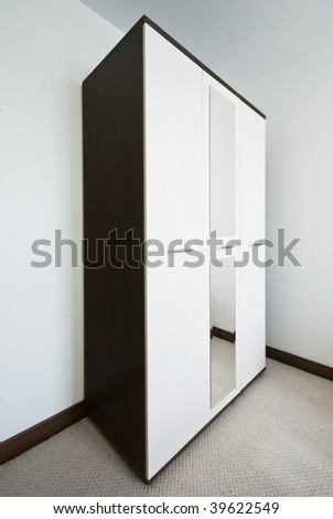 modern wardrobe with mirror on the white wall back round - stock photo
