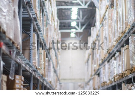Modern warehouse with cardboard boxes and rows of shelves - stock photo