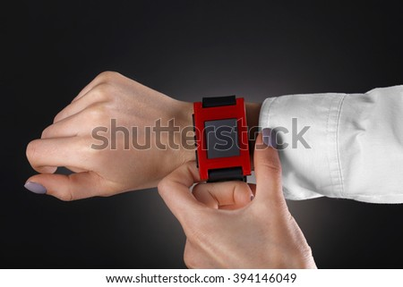 Modern watch on a woman's wrist over black background - stock photo