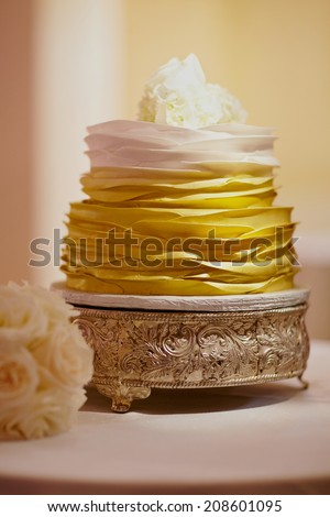 Modern wedding cake on reception table with dramatic lighting - stock photo
