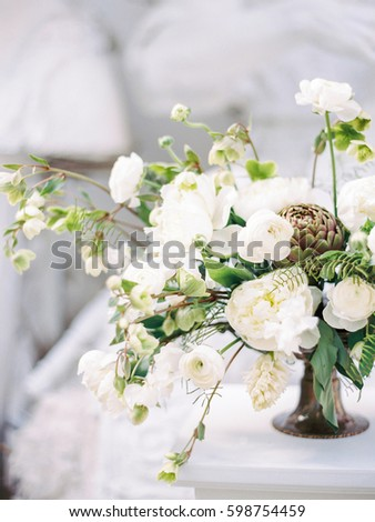 Modern wedding white flower bouquet of the bride with artichoke near a marble stone on a grey background