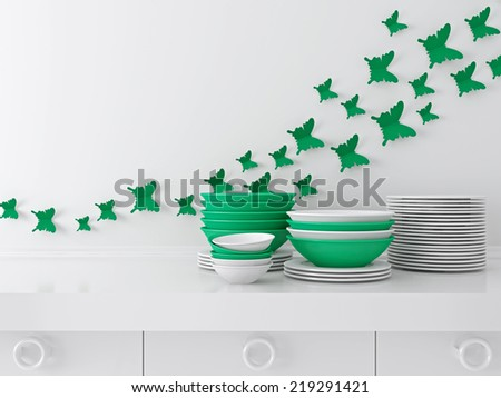 Modern white and green kitchen design. Ceramic kitchenware on the worktop. Butterfly decor on the wall. - stock photo