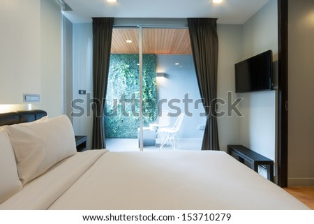 modern white bedroom in apartment with space for terrace. - stock photo