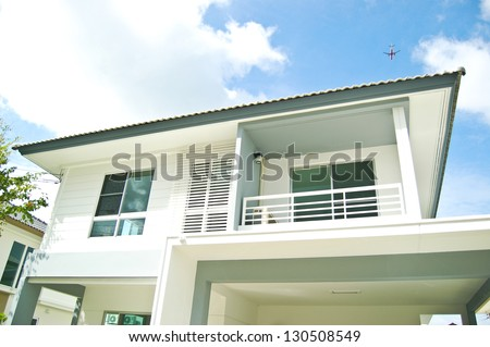 Modern white building with balcony on a blue sky - stock photo