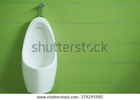 Modern white ceramic urinals in men's bathroom on green tiles background  - stock photo