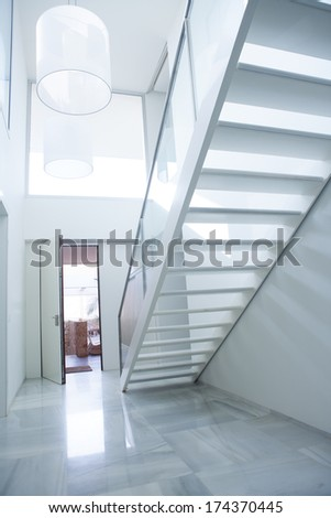 Modern white house entrance hall lobby with stairway and light coming in - stock photo