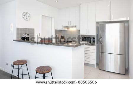 Modern white Kitchen in apartment with Polished Stainless Steel Appliances - stock photo
