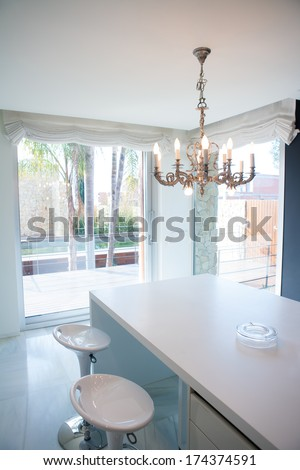 Modern white kitchen table with vintage chandelier and stools - stock photo