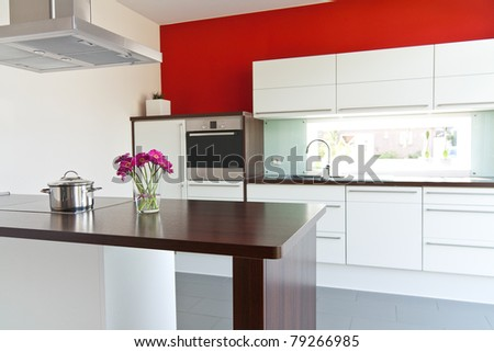 Modern white kitchen with red wall in the back - stock photo