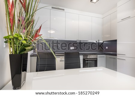 Modern white kitchen with white table and flowers - stock photo