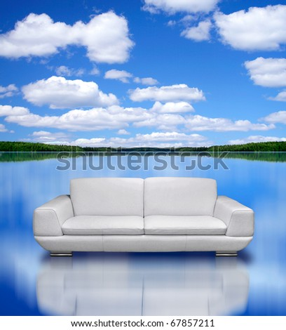 Modern white leather sofa and silver plated frame in room with dark lilac damask pattern wall - stock photo