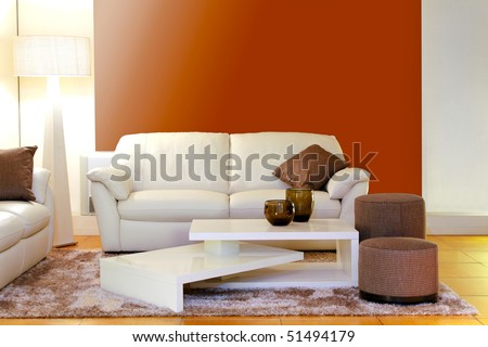 Modern white leather sofa with interesting coffee table - stock photo