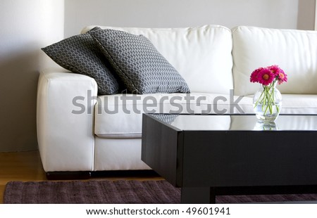 modern white living room with vase of pink daisies - stock photo