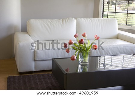modern white living room with vase of red tulips - stock photo