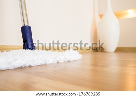 Modern white mop cleaning wooden floor from dust - stock photo