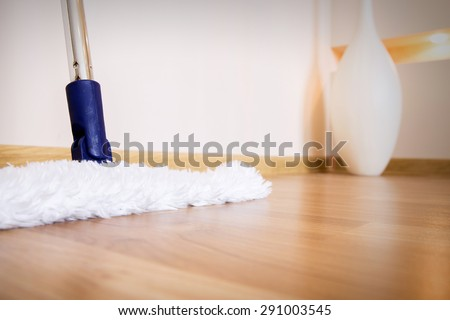 Modern white mop cleaning wooden floor from dust, house supplies - stock photo