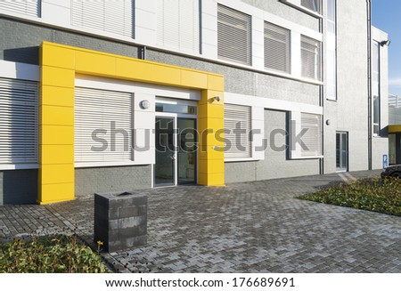 modern white office building with yellow entrance - stock photo