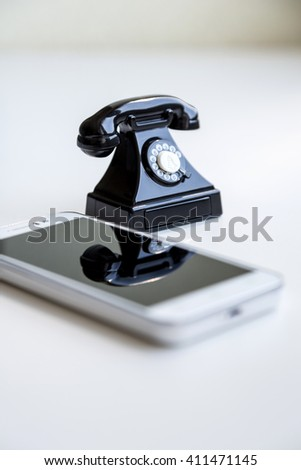 Modern white smartphone and toy retro telephone standing together on a white background as a symbol of technological evolution - stock photo