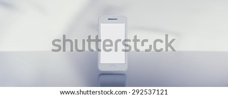 Modern white smartphone on reflective steel surface. Image easy to crop to achieve empty space for text on right or left side.