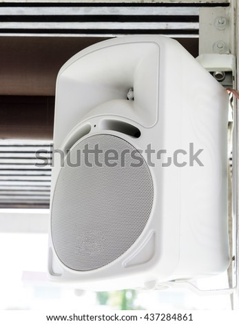 Modern white speaker is hanging on the metal pole of the travel bus. - stock photo