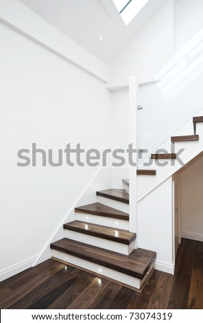 modern white staircase with wooden floor and glass barrier - stock photo