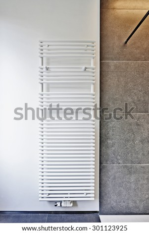 modern white towel rail mounted on wall - stock photo