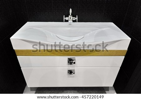 Modern White Vanity Basin Unit In Black Tiled Washroom Or Bathroom - stock photo