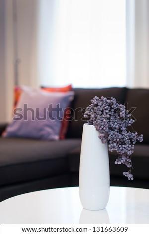 Modern white vase with violet flower in living room - stock photo