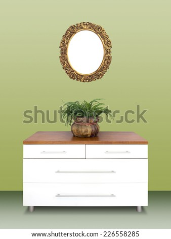 Modern white wooden chest of drawers and Antique gilded Frame on a green wall - stock photo