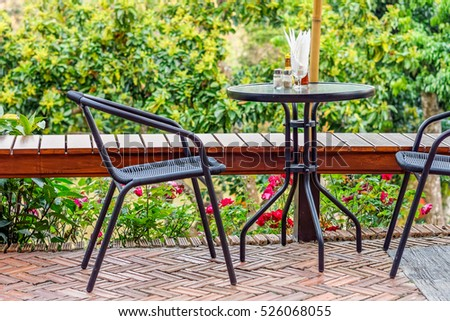 Modern wicker metal chairs and round table with condiments. They are on a terrace or patio of  a restaurant.