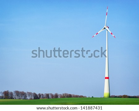 modern wind generator in front of blue sky - stock photo