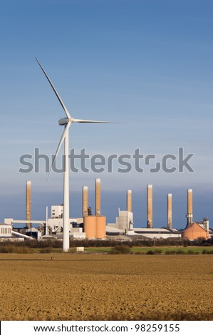 Modern wind turbine with old factory behind it vertical - stock photo