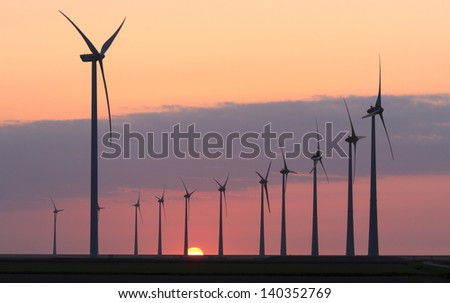 Modern wind turbines near the Eemshaven (the Netherlands) producing 'green' energy during sunset. - stock photo