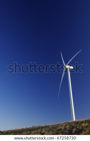 modern windmill for electricity production and grassland - stock photo