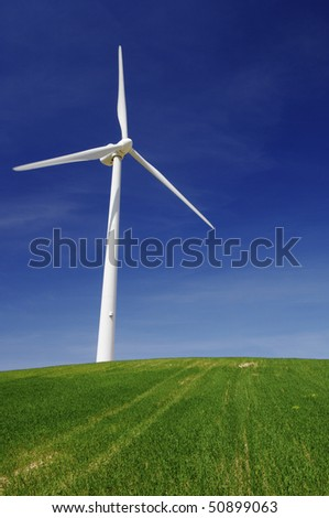 Modern windmill on a green hill with blue sky - stock photo
