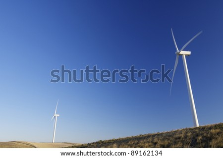 modern windmills for electricity production and grassland - stock photo