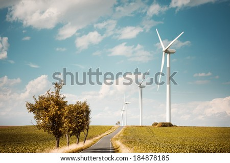 Modern windmills generate electric power along contry road, text space - stock photo