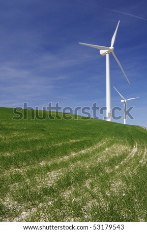 modern windmills in a green meadow with cloudy sky