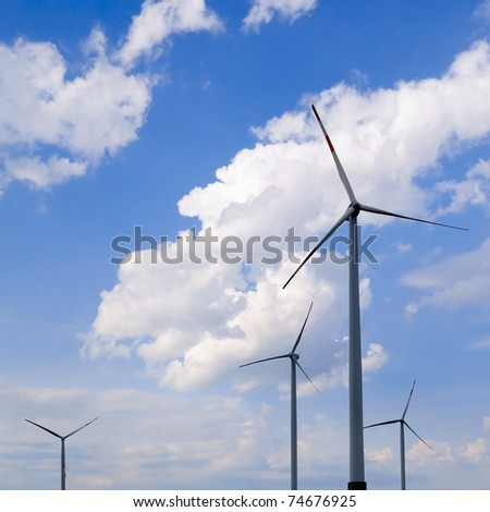 Modern windmills under dramatic sky, square framing